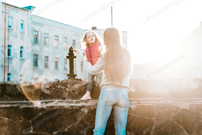 Mom and daughter sit together on the fence