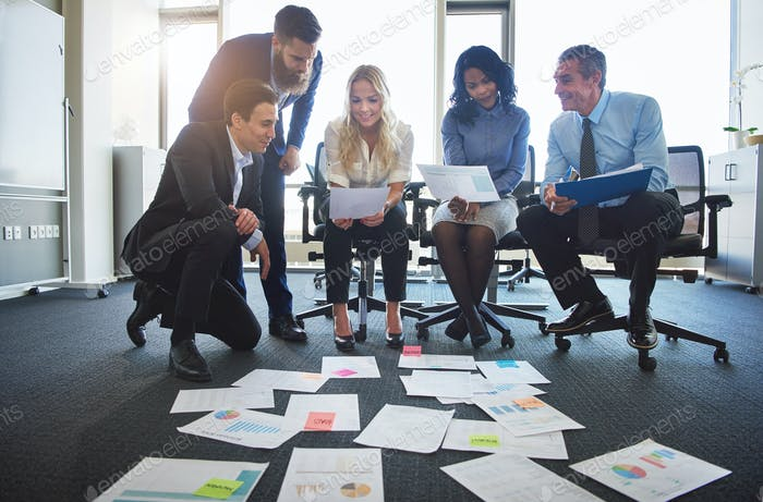 Diverse businesspeople discussing paperwork laid out on an office floor