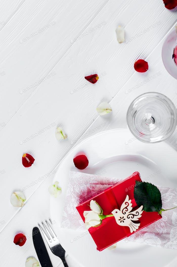 Элегантный праздничный стол с подарком красной лентой