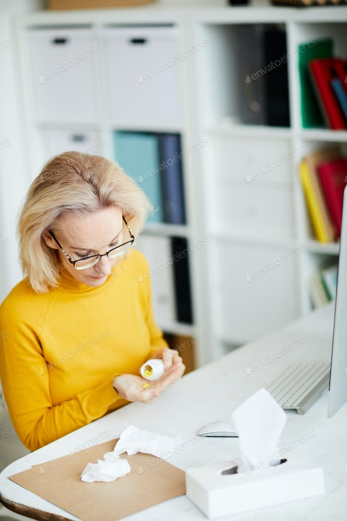 Woman Taking Pills at Workplace