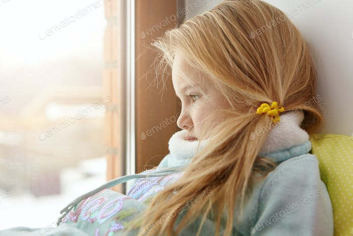 Home alone. Sad cute female child with blonde hair sitting on windowsill, looking out window with un