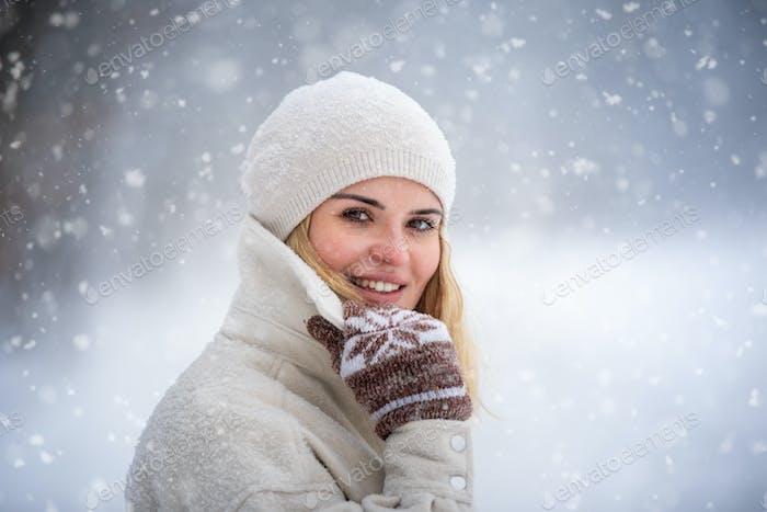 Красивая женщина зимой среди снега