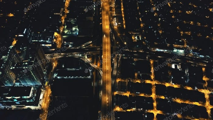 Aerial night city traffic road at business center. Amazing urban scene of metropolis centre highway