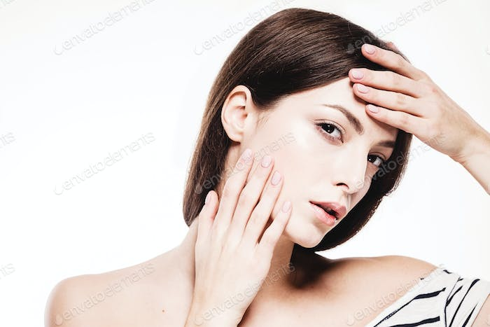Beauty woman face portrait. Beautiful spa model girl with perfect fresh clean skin touching her face