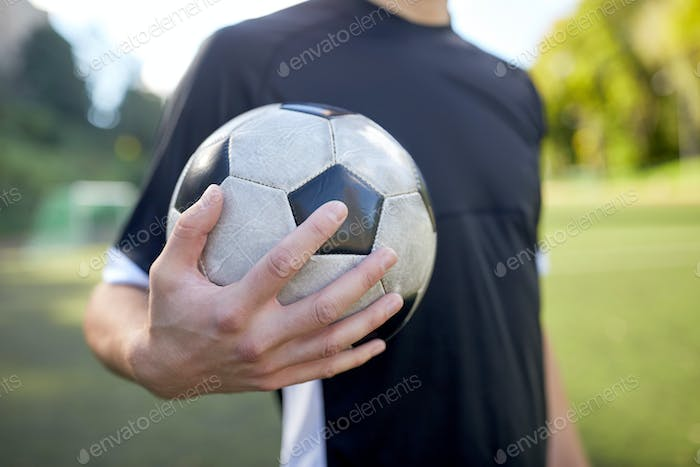 close up of soccer player with football on field