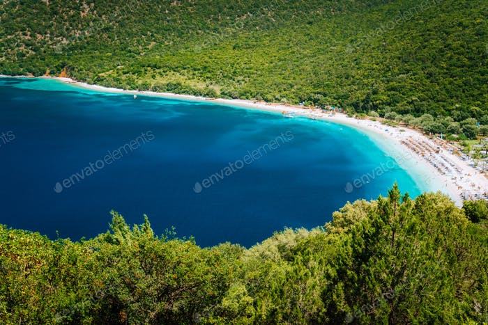 Sunny summer day on Antisamos beach on Kefalonia island, Greece. Crystal clear water, huge hills