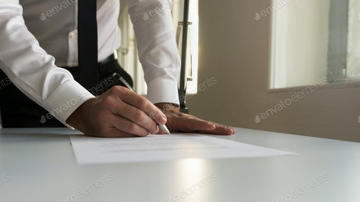 Businessman in office signing contract, document or legal papers
