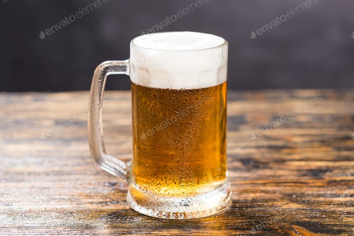 Cold glass of lager beer with foam and dew on wooden table