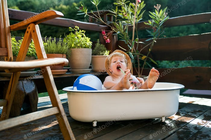 Small boy with a hat in bath outdoors in garden in summer, playing in water.