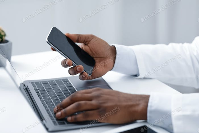 Close up of doc hands holding phone and using laptop