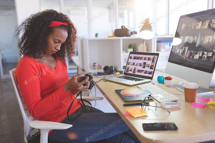Young female graphic designer reviewing photos in digital camera at desk