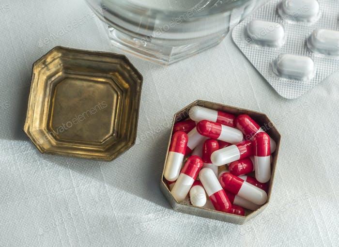 Metallische Pillenbox mit weißen und roten Kapseln zusammen mit Wasserglas