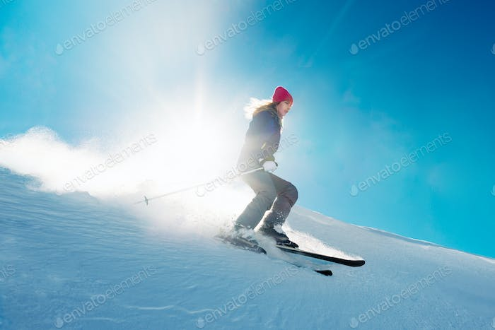 skier is riding from snow hill in the sun beam