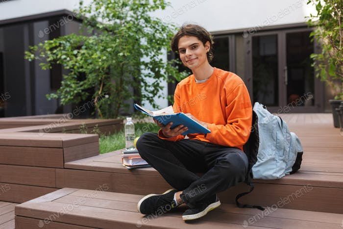 Young smiling student sitting with book in hands and happily looking in camera