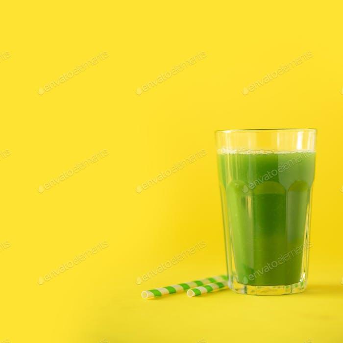 Glas grüner Sellerie Smoothie auf gelbem Hintergrund. Banner mit Kopierraum. Quadratische Ernte. Vegan