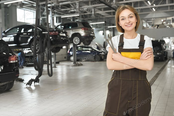 Young positive woman in coverall working in auto service
