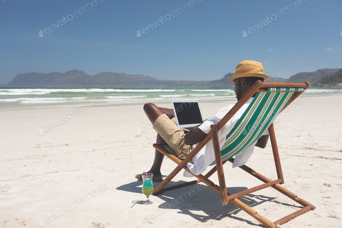 Man using laptop while sitting at sun lounger at beach on a sunny day