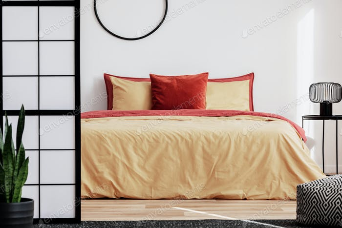 Comfortable bed with yellow and red bedding, industrial lamp on bedside table