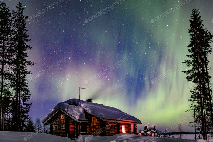 Polar arctic Northern lights Aurora Borealis activity over wooden cottage in winter Finland, Lapland
