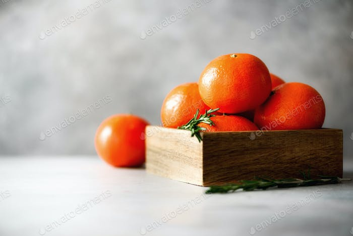 Orange tangerines, mandarins, clementines, citrus fruits with rosemary in wooden box on grey