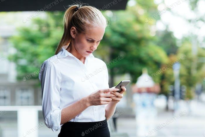 Nachdenklich junge Geschäftsfrau halten Handy und Eingabe Nachricht