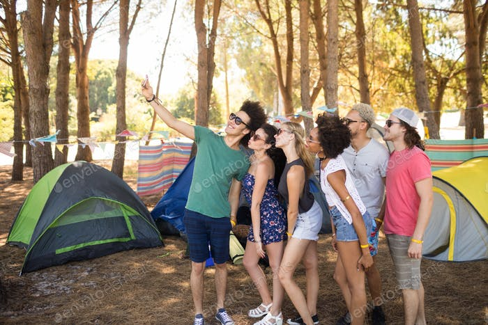 Smiling friends taking selfie at campsite