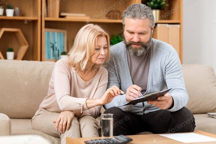 Mature husband and wife reading terms of contract before signing it
