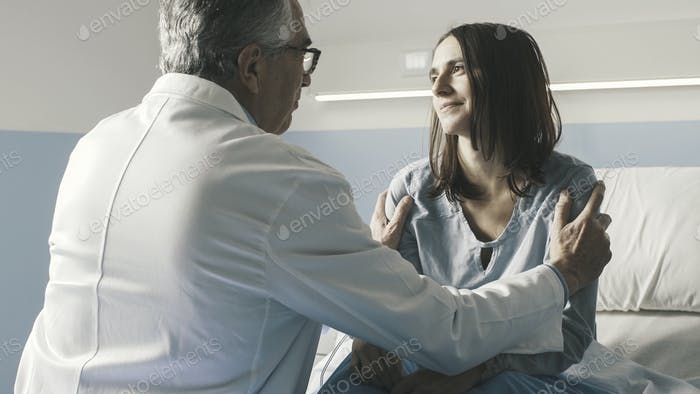 Caring doctor cheering up a patient at the hospital