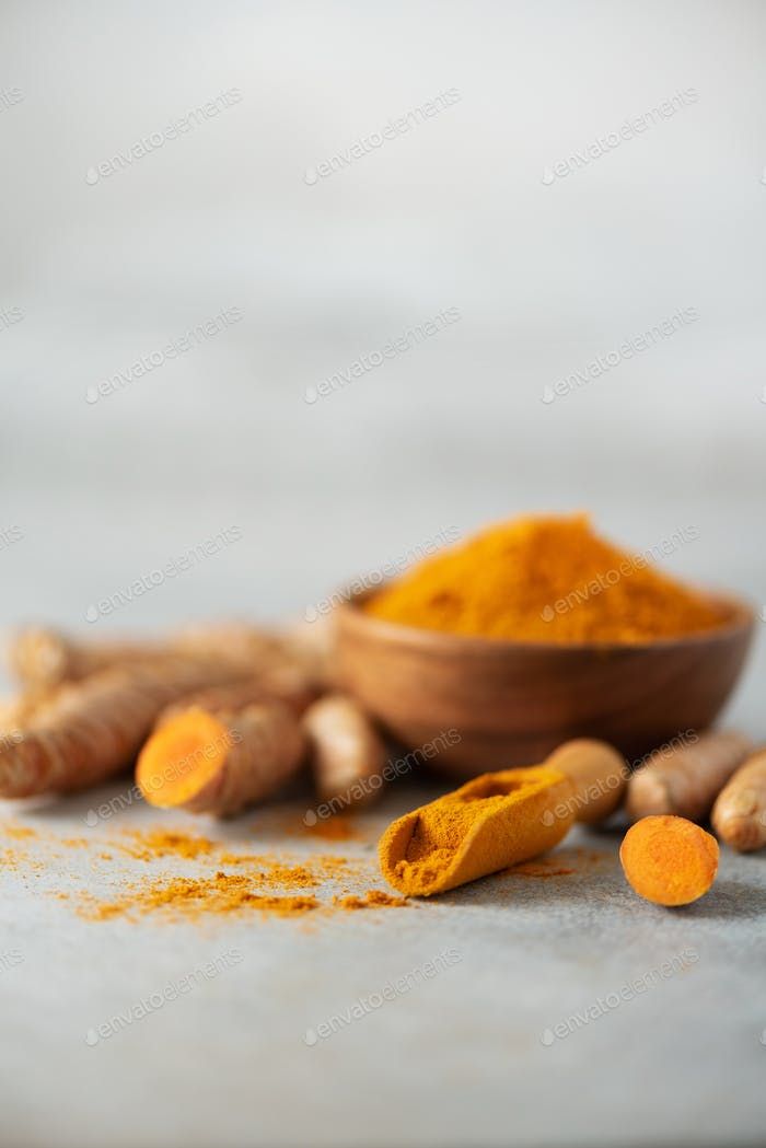 Turmeric powder in wooden bowl and fresh turmeric root on grey concrete background. Banner with copy