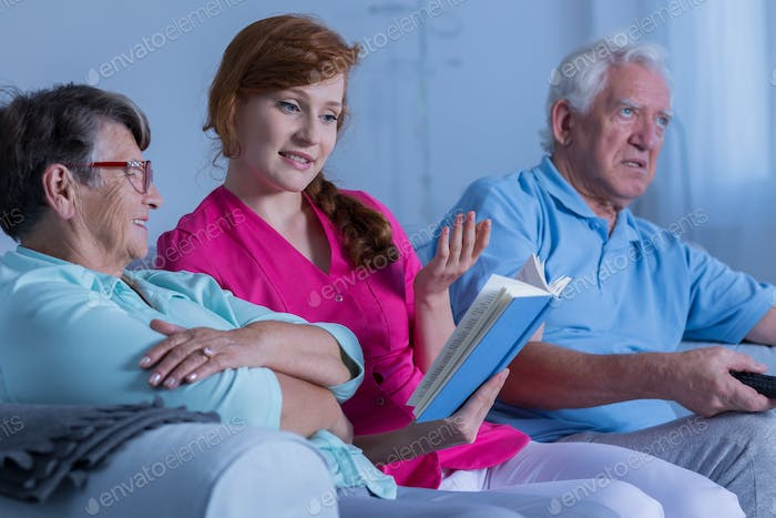 Caregiver reading to elderly woman