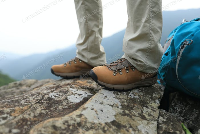 Hiking legs standing on mountain top cliff edge