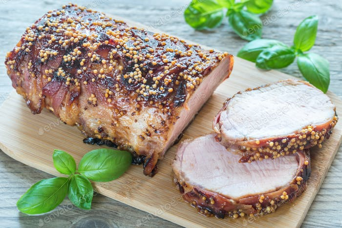 Baked pork meat wrapped in bacon
