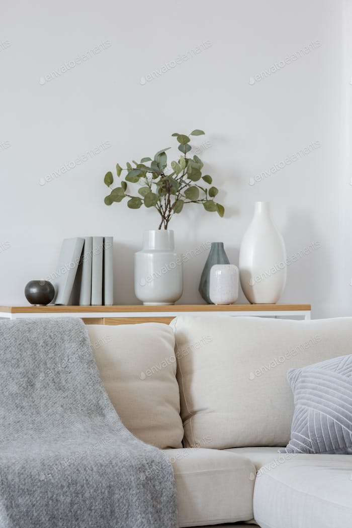 Green flowers in grey vase next to books on wooden console table in bright living room interior