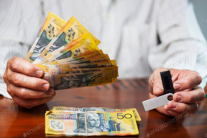 Man`s hands are holding australian dollars and nano wallet