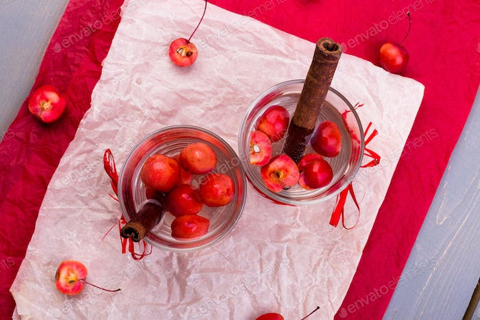 Detox apple cinnamon water on red pepper and wooden background. Top view. Flat lay.