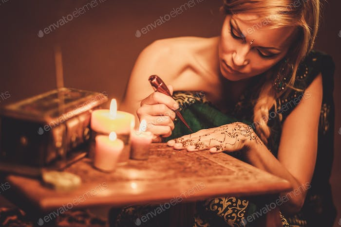Woman drawing f henna menhdi ornament on her hand