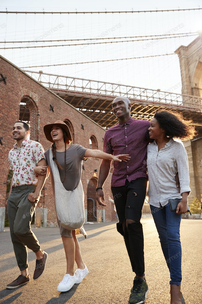 Group Of Friends Walking By Brooklyn Bridge In New York City