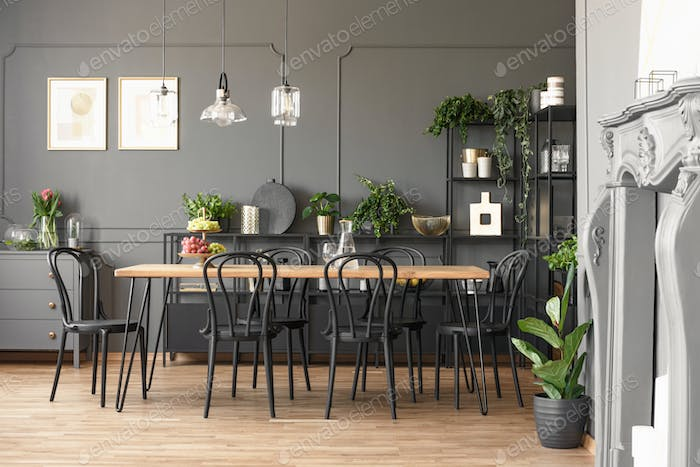 Lamps Above Wooden Table And Black Chairs In Grey Dining Room
