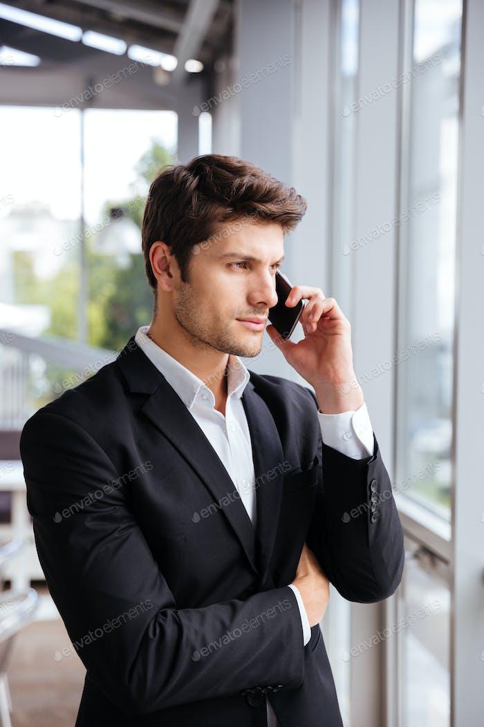 Hombre de Empresario joven serio hablando por teléfono celular en la oficina