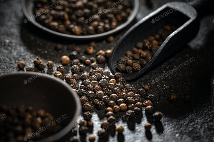 Black peppercorns in black wooden shovel