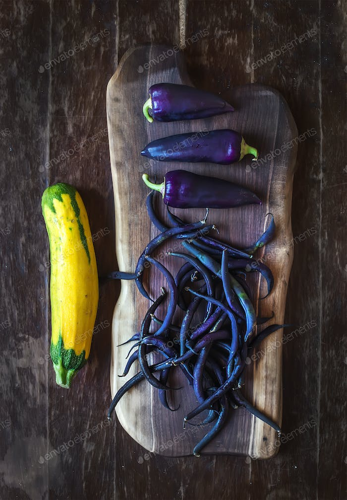 Violet chili peppers, beans and yellow zucchini on rustic wooden chopping board