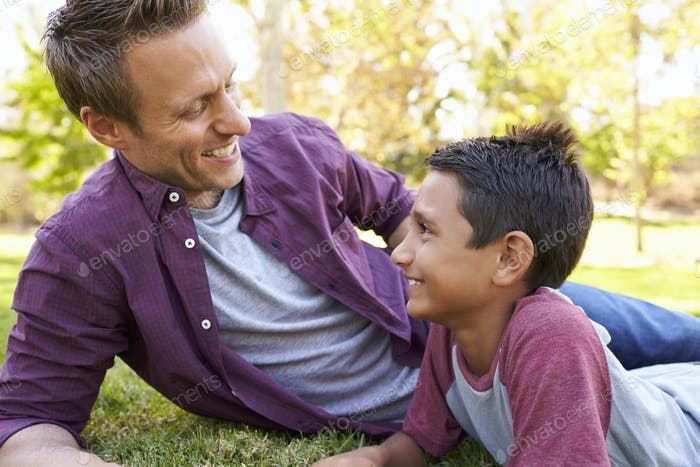 Mixed race Asian boy relaxing in park with his white father