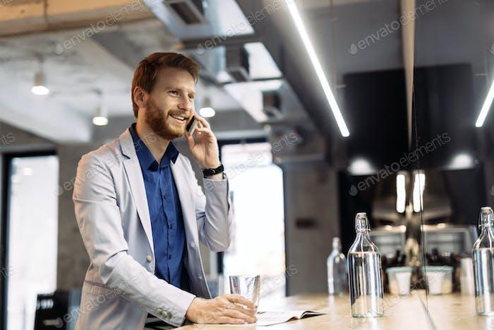 Handsome businessman using smartphone in pub