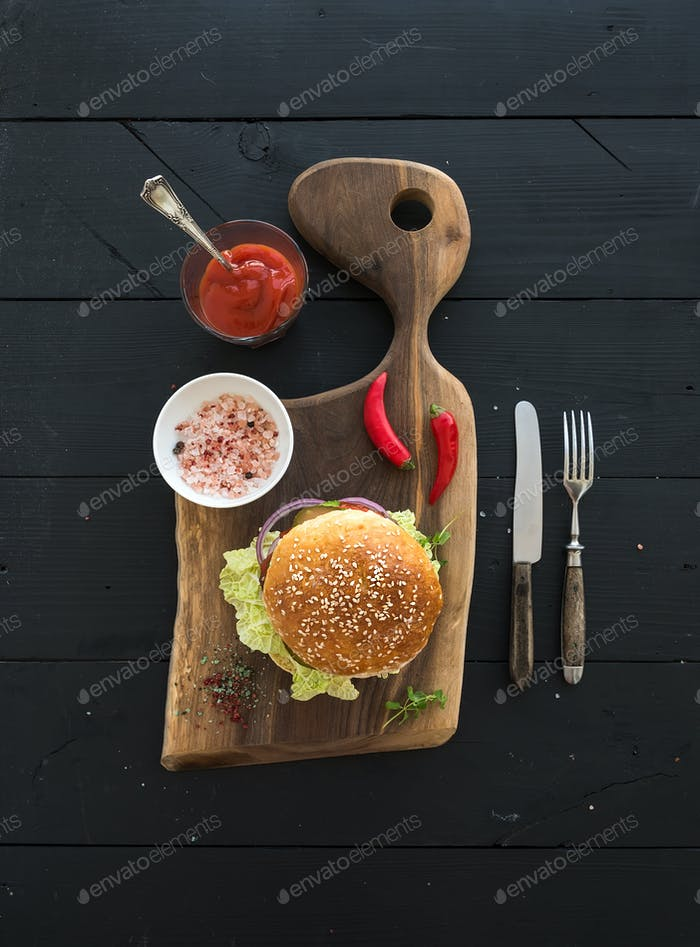 Fresh homemade burger on dark serving board with spicy tomato sauce, sea salt