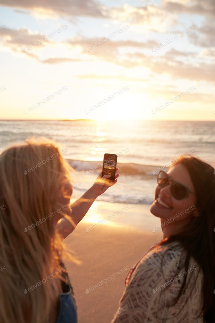 Girls taking a photo of the sunset with mobile phone