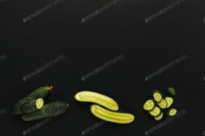 Whole and cut cucumber on black isolated background