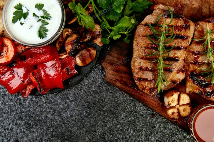 Steak pork grill on wooden cutting board with a variety of grilled vegetables