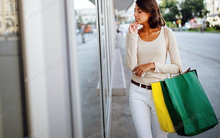 Schöne Frau mit Einkaufstaschen in der ctiy. Verkauf, Shopping, Tourismus und Happy People Konzept