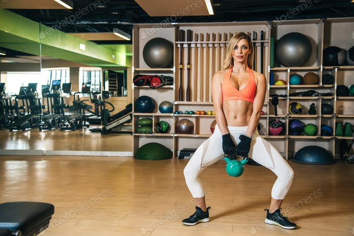 beautiful blonde woman in the gym training lifting weights working out