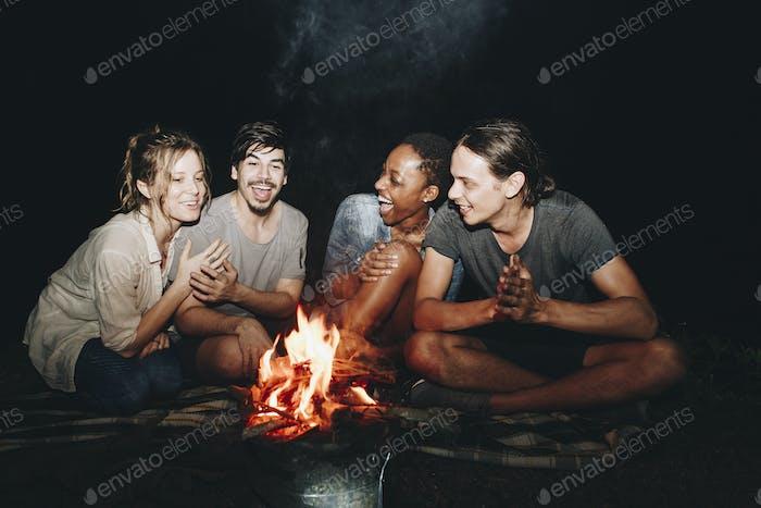 Gruppe von Freunden sitzen um ein Lagerfeuer auf einem Campingplatz
